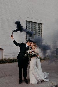 Bride and Groom kiss while bride holds big bouquet and groom holds black smoke bomb in the air