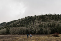 couple running in field during hood river engagement session