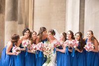 Bride and Bridesmaids laughing while holding flowers