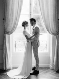 Young married couple embrace in front of window during anniversary photo session in French manor