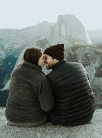 man & woman sitting on cliff smiling