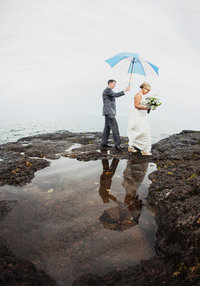 A bride and groom are walking under an umbrella on the rocky shore of Lake Superior at Larsmont Cottages