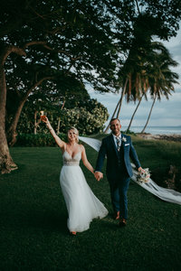 bride and groom holding hands and walking next to ocean
