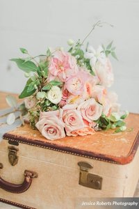 A tan suitcase with bouquet of flowers on top.