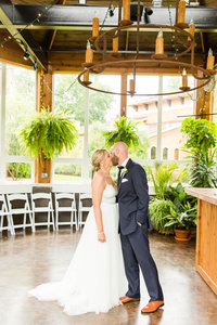 Bride and groom kissing at the Conservatory at Gervasi Vineyard photographed by akron ohio wedding photographer