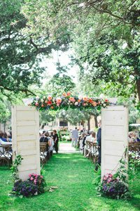 Vintage doors open to an outdoor wedding.