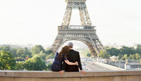 Husband and wife embrace in front of Eiffel Tower