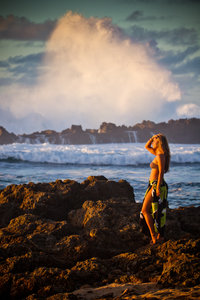Hawaiian girl at the beach with huge crashing waves.