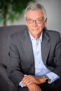 Headshot of Financial Advisor from Rae Lipskie wearing a business suit and tie, sitting in grey chair in front of plant in photography studio KW Headshots.
