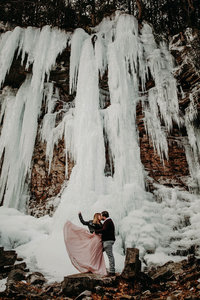 couple standing under frozen waterfall