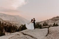 bride and groom standing on rock with mountain in background