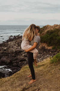 couple kissing next to rocks