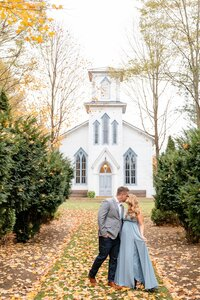 Guy-kisses-his-fiance-in-front-of-the-Cranberry-Creek-Gardens-Chapel-during-their-fall-engagement-session