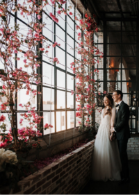 flower wall by windows with a bride and groom