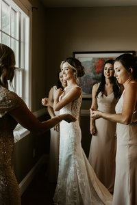 bride megan coolbaugh surrounded by her sisters and mom while they help her get ready at the house mountain inn in lexington virginia