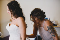 Bride getting ready with bridesmaid tying up dress