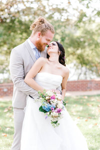 Bride and groom posing with colorful bouquet