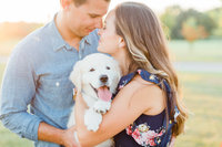 engaged couple poses for photos with their puppy