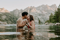 man and woman kissing in water