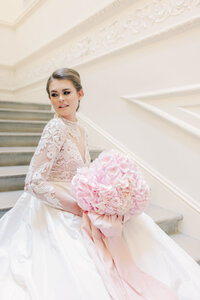Portrait of bride in ivory wedding gown sitting on marble stair case