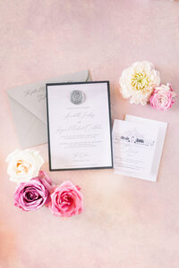a wedding invitation suite styled on a pink backdrop.
