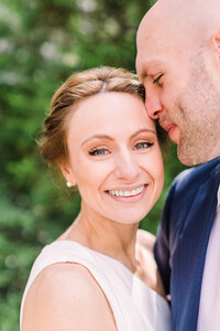 Bride smiles in camera as groom nuzzles her cheek