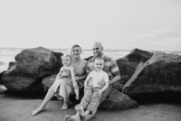 family of four sitting on rocks at beach