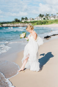 Bride touches the ocean with her toes on her wedding day.