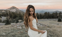 bride holding side of dress while standing in field with mountains in the background