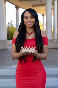 Black woman in red dress with crown