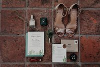 Bride's wedding details like shoes, invitation, perfume, and rings are styled on red tile floor