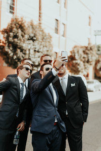 Men in suites taking a selfie