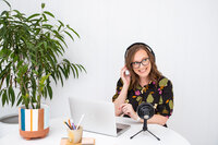 Melissa-Packham_A-Brand-Is-Not-A-Logo_Melissa-sitting-at-table-with-plants-laptop-wearing-headphones-podcast-mic-listening-looking-left-smiling_Landscape