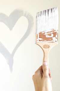 A used pain brush held next to a heart painted on a wall.
