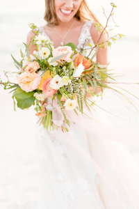 Bride holds bouquet in front of her.