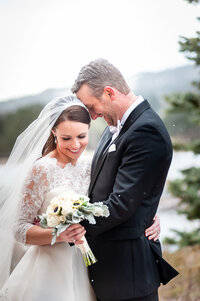 A Bride and Groom Embrace with Big Smiles Just After Their First Look While It Snows on Them