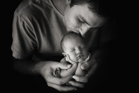 In-studio portrait of newborn baby held by dad, black and white photo