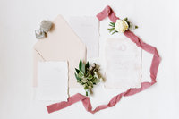 Elegant wedding stationary spread out with a mauve ribbon, Mrs. Box and beautiful White Rose boutonniere.