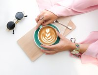 Woman with pink sleeves holding a cup of coffee on white table