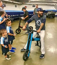 Tampa Bay Rays Sergio Romo sitting on Blue Go-Bike M2 with his kids next to him
