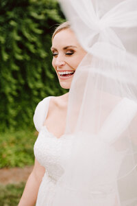 candid laughing bride with veil flowing in the wind at wilburn street studio nashville wedding