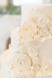 Three tiered wedding cake with ivory icing decorated with cascade of various floral designs made from ivory icing taken by New Orleans wedding photographer Elizabeth Collins
