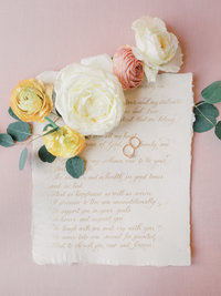 pair of wedding rings photographed on hand written vows and accented with cream and blush flowers
