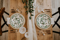 two china plates on a wood table with a cream table runner