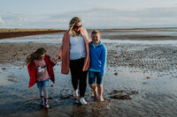 mother and her two young children stroll hand in hand along troon beach