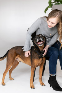 A woman in a gray shirt looking down on her brown, orange dog