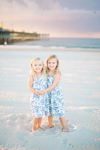 young sisters smiling and holding hands on the beach at Myrtle Beach State Park