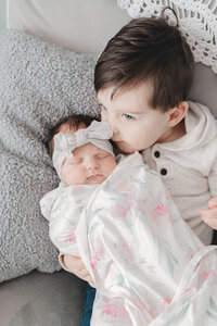 brother cuddling newborn sister at lifestyle newborn session in dallas