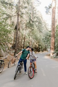 bride and groom kissing during their bike ride engagement photos in yosemite
