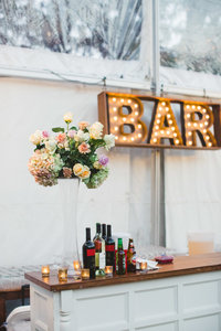 A vintage bar with flowers and bottles on top.